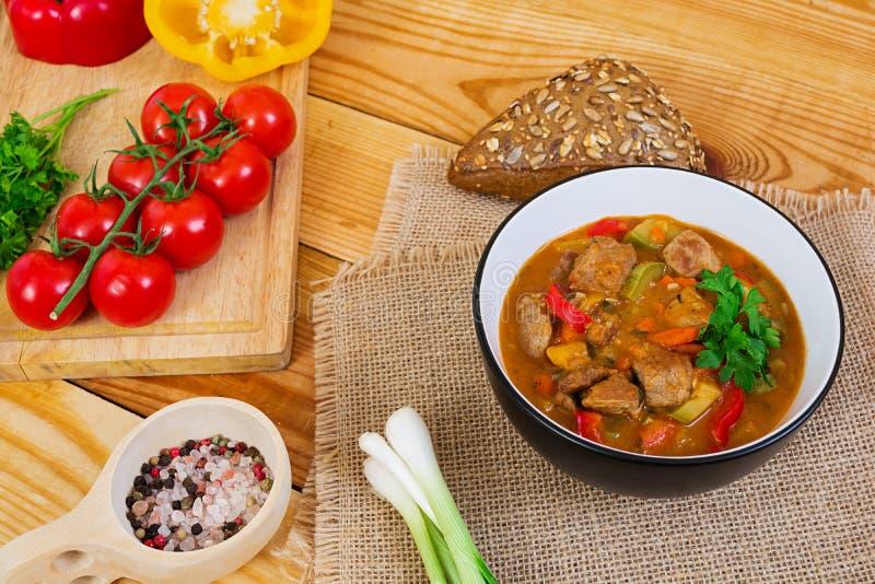 Ragu med kött och grönsaker i tomatsås på träbakgrund royaltyfria bilder