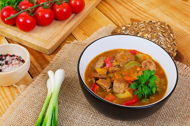 Ragu med kött och grönsaker i tomatsås på träbakgrund arkivfoton