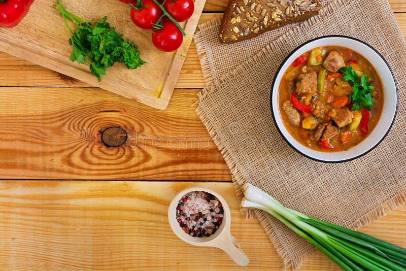 Ragu med kött och grönsaker i tomatsås på träbakgrund Top besk?dar arkivbild