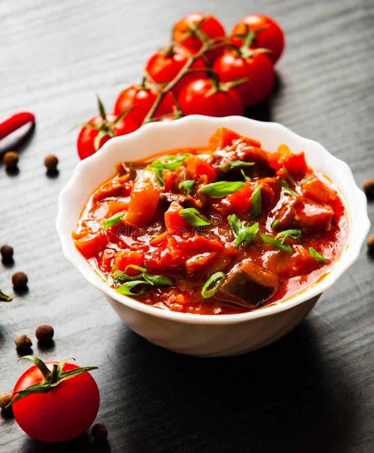 Rague végétal avec l'aubergine, le poivre, la tomate et la carotte dans la cuvette blanche sur le fond en bois foncé photos stock