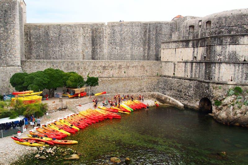 Ragusa, Croazia - 2 giugno 2017: Il lotto dei kayacs rossi e gialli ha tirato la riva vicino alla parete di vecchia fortezza di R fotografie stock libere da diritti