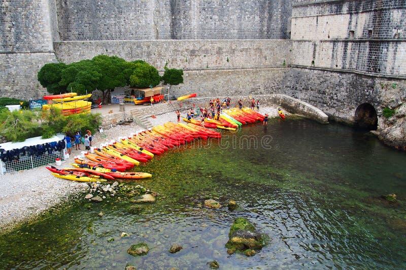 Ragusa, Croazia - 2 giugno 2017: Il lotto dei kayacs rossi e gialli ha tirato la riva vicino alla parete di vecchia fortezza di R immagini stock