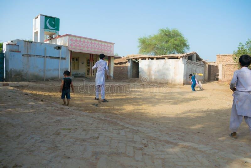 Rahimyar可汗,旁遮普邦,巴基斯坦7月1,2019:打墙网球的一些地方男孩在村庄 库存图片