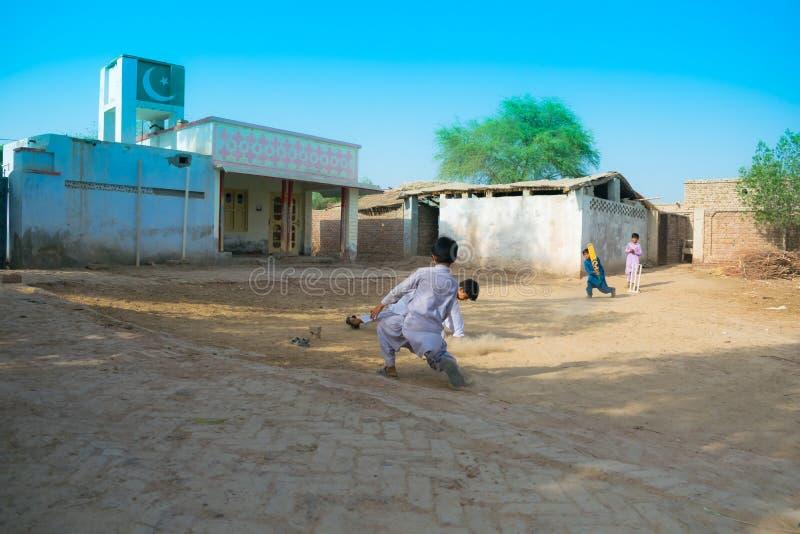 Rahimyar khan, punjab, Pakistan-juli 1,2019: några lokala pojkar som spelar syrsan i en by arkivfoton