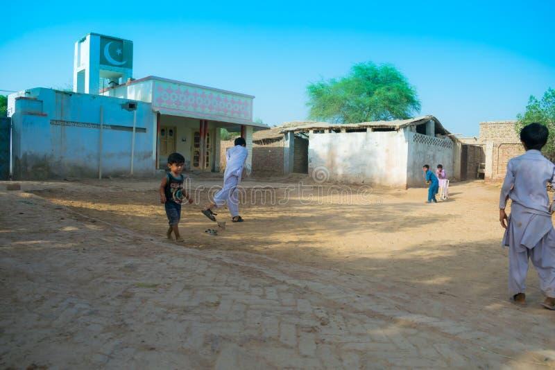 Rahimyar khan, punjab, Paquistão-julho 1,2019: alguns meninos locais que jogam o grilo em uma vila imagens de stock royalty free