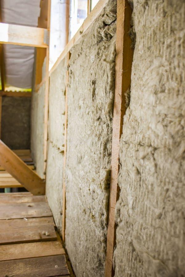 Rahmen der Hausmauer, der Bretter und des Bauholzes, ein Fenster, eine graue Dampfsperre vom Innere, Nicht-planierte Bretter sind lizenzfreies stockbild