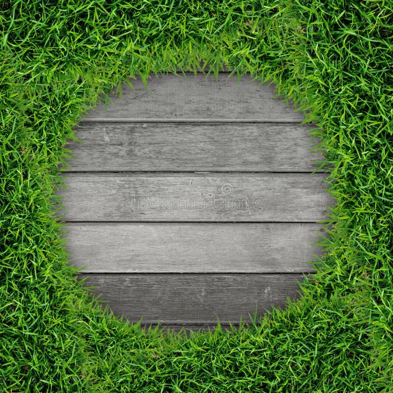 Rahmen des grünen Grases und Weinleseholzhintergrund stockfotografie