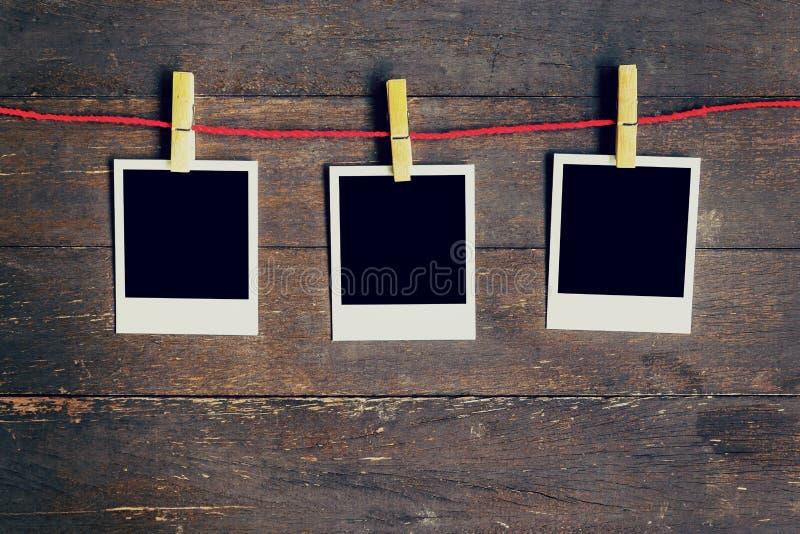 Rahmen mit drei leerer Fotos, der an der Wäscheleine hängt Auf altem Holz lizenzfreie stockfotografie