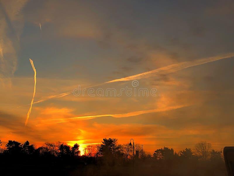 Raias amarelas da luz com nascer do sol alaranjado foto de stock