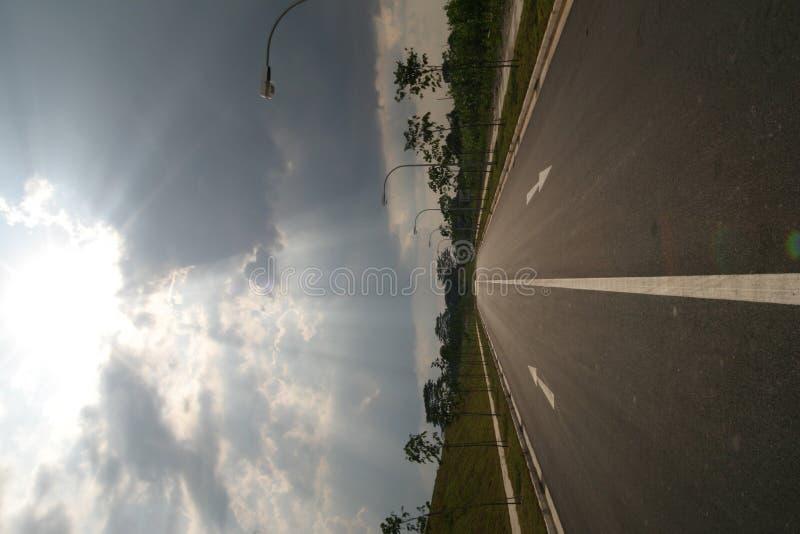 Raias de Sun na estrada vazia fotografia de stock royalty free