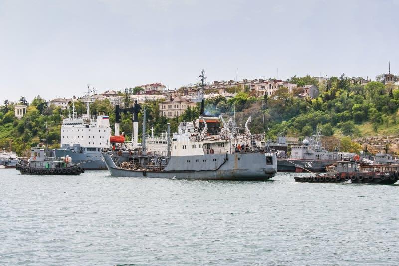 Raid tug. `RB-247` pulls a small sea tanker `VTN-99` of the Chernomorsky naval fleet in the bay of Sevastopol. Crimea, Ukraine. May, 2009 stock image