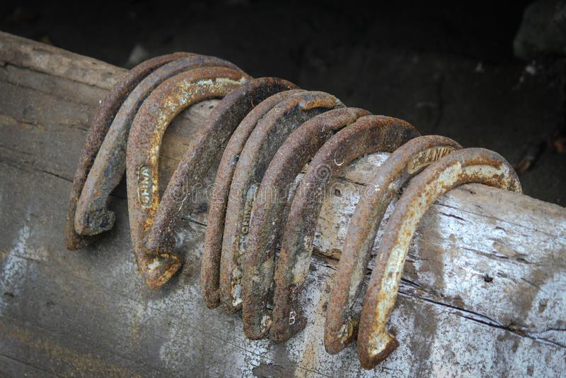 Rail de barrière en bois tenant dix chaussures antiques chanceuses de cheval images stock