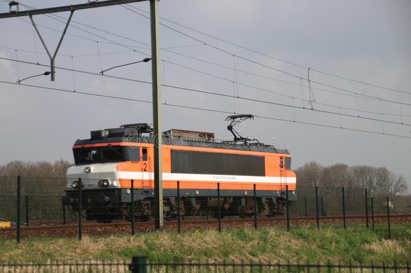 Rail force locomotive 1831 in orange and white on railroad track between gouda and Rotterdam at Moordrecht. stock photography