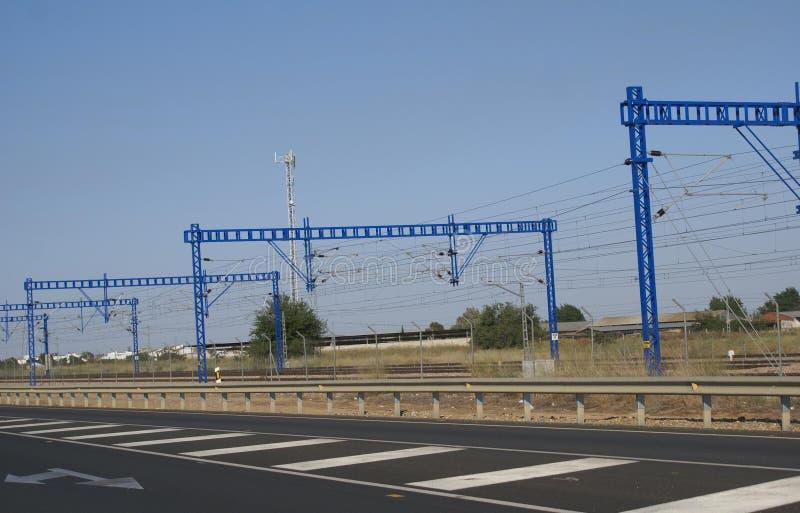 Rail monterade lastningsbryggakranar bredvid en motorway eller en huvudväg royaltyfri foto