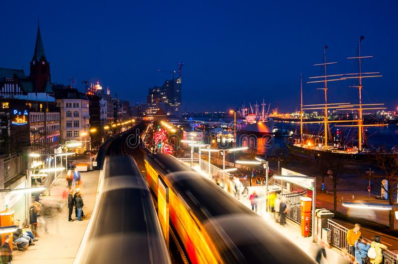 Rail station at night with port, boats, modern buildings in Hamburg, Germany. Hamburg, Germany. Rail station at night with port, boats, modern buildings in royalty free stock photo