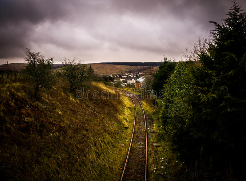 Rail Track on a cloudy day. This rail track runs throughout South Ayrshire, Scotland. Very cloudy and damp day. The small gap in the clouds lit up a portion of stock photo