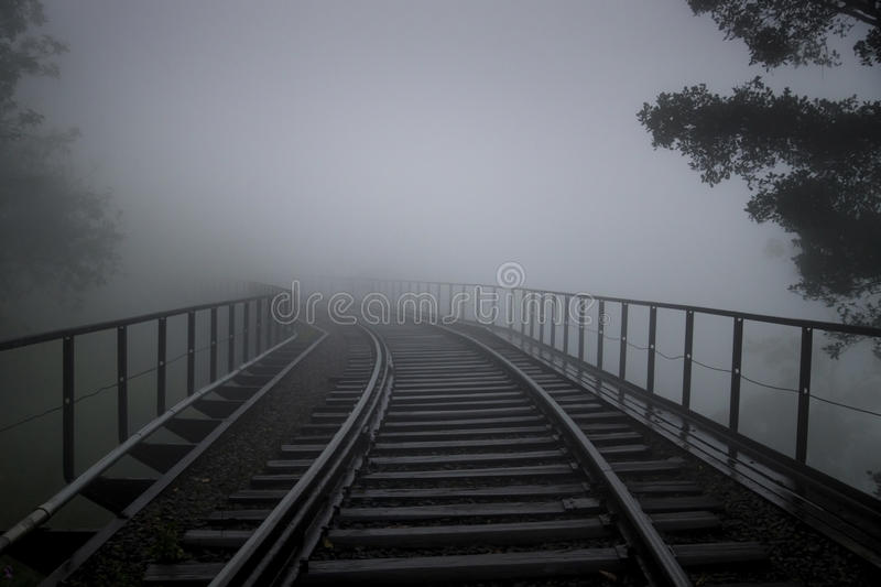 Rail tracks in the fog, Ella, Sri Lanka. Rail tracks on a bridge in the fog, with some trees and handrails stock images