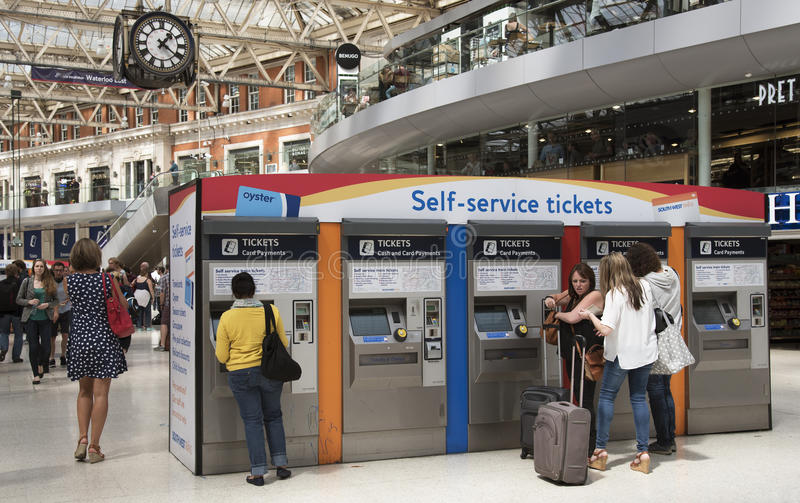 Rail travellers buying tickets. Rail travellers purchasing railway tickets from a self service machine on station concourse royalty free stock photos