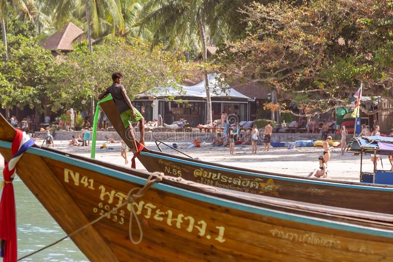 Railay, Krabi Province, Thailand - February 17, 2019:  A young sailor moored to the shore and tied on the bow of a long-tailed stock photos
