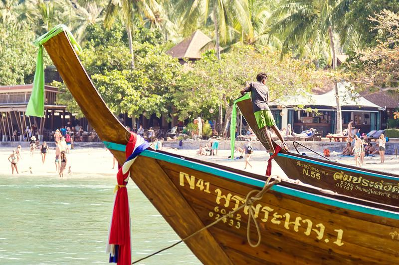 Railay, Krabi Province, Thailand - February 17, 2019:  A young sailor moored to the shore and tied on the bow of a long-tailed royalty free stock images