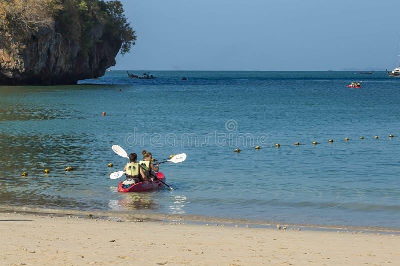 Railay, Thaïlande - 19 février 2019 : Un jeune couple, un homme et une fille, bain dans un kayak du rivage pendant le matin Ils s photo libre de droits
