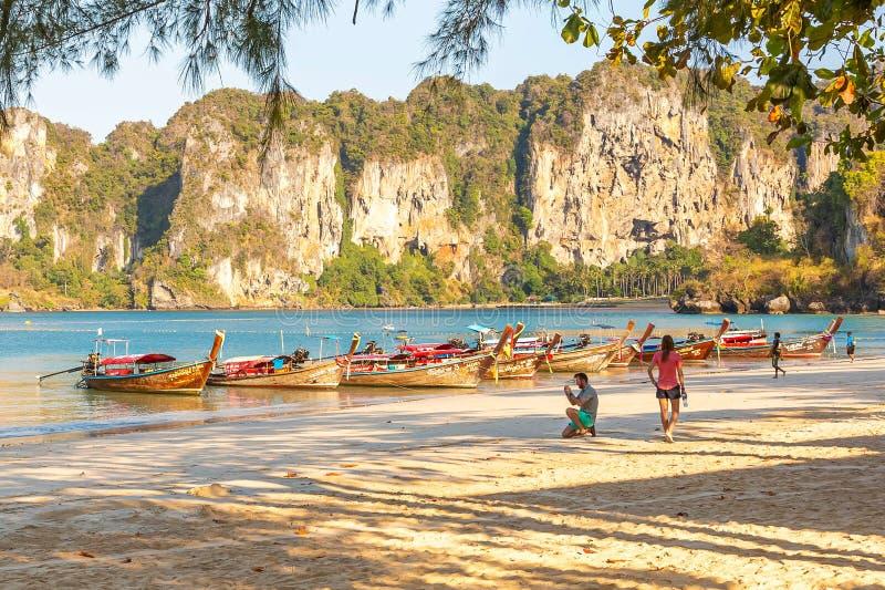 Railay Thailand - Februari 19, 2019: En man fotograferar fartyget på stranden som huka sig ned på ett knä Bred sandig tropisk str royaltyfri foto