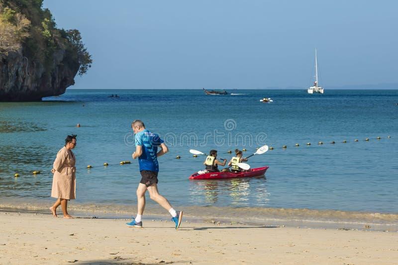 Railay Thailand - Februari 19, 2019: En man kör ner stranden i morgonen En kvinna promenerar den sandiga kusten I vattnet fotografering för bildbyråer