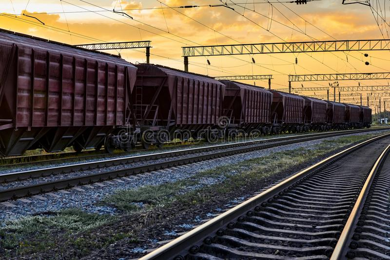 Railcar for dry cargo during beautiful sunset and colorful sky, railroad infrastructure, transportation and industrial concept royalty free stock photography