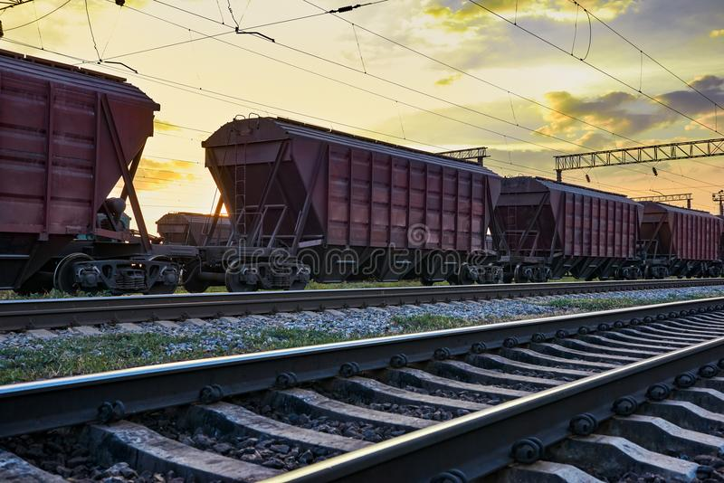 Railcar for dry cargo during beautiful sunset and colorful sky, railroad infrastructure, transportation and industrial concept stock photography