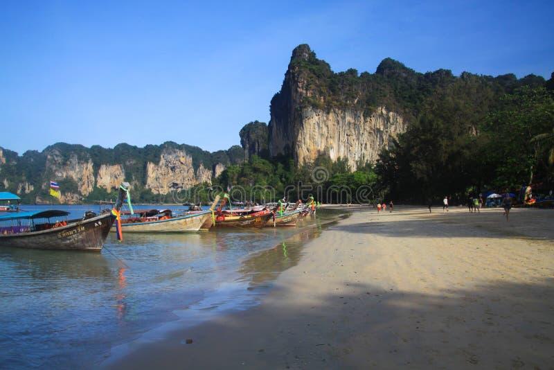 RAILEY KRABI, THAILAND - JANUARI 3 2017: Weergeven op afgezonderd strand met hoge steile kalksteenklippen en traditionele Thaise  stock afbeeldingen
