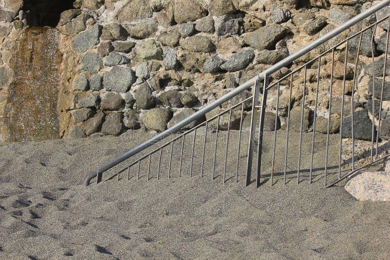 Railing under the sand on the beach stock photos