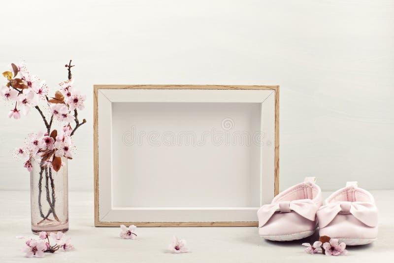 Raillez avec le cadre de tableau vide, les fleurs tendres roses de ressort et les petites chaussures de bébé photo stock