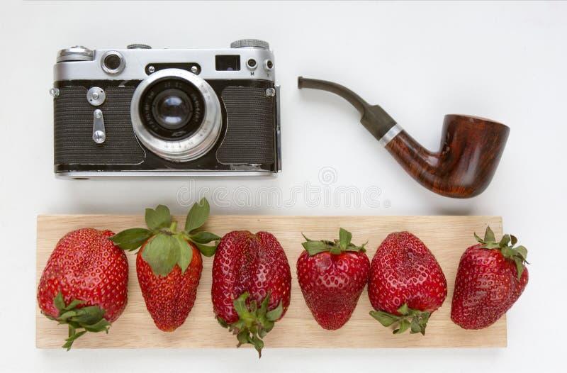 Raillez pour l'illustration avec le vieil appareil-photo, les fraises rouges et le tuyau de tabagisme Vue supérieure Place pour l photos stock