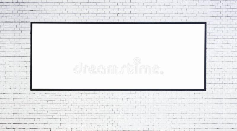 Raillez vers le haut de la bannière vide avec le cadre noir sur le mur de briques blanc images stock