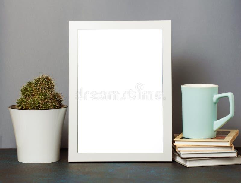 Raillez vers le haut de la photo avec le cadre et la tasse de thé ou café et livres et cactus Fin vers le haut images libres de droits
