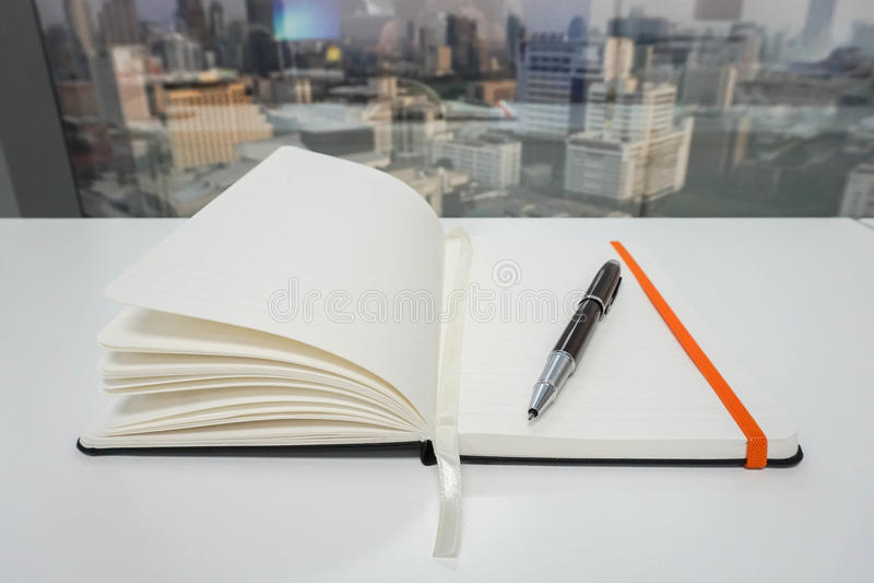 Raillez vers le haut du bloc-notes pour prendre des minutes avec le stylo de luxe dans le bureau image stock