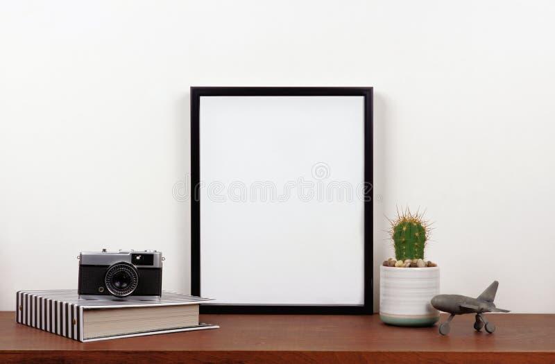Raillez vers le haut du cadre noir contre le mur blanc avec le décor de voyage sur une étagère en bois images libres de droits