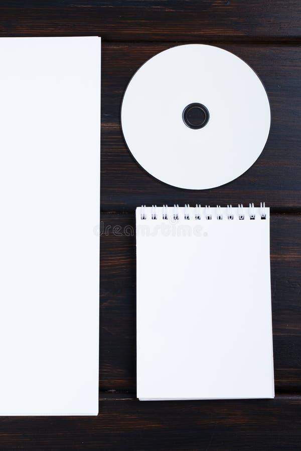 Raillez vers le haut du carnet vide, disque CD, le stylo, liste de papier sur le bureau en bois photo stock