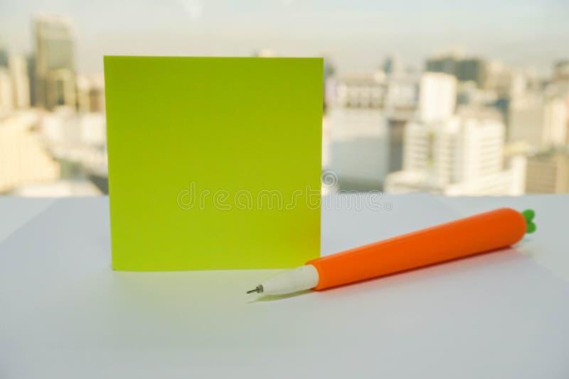 Raillez vers le haut du post-it sur le bureau avec le stylo mignon de carotte pour noter photographie stock libre de droits