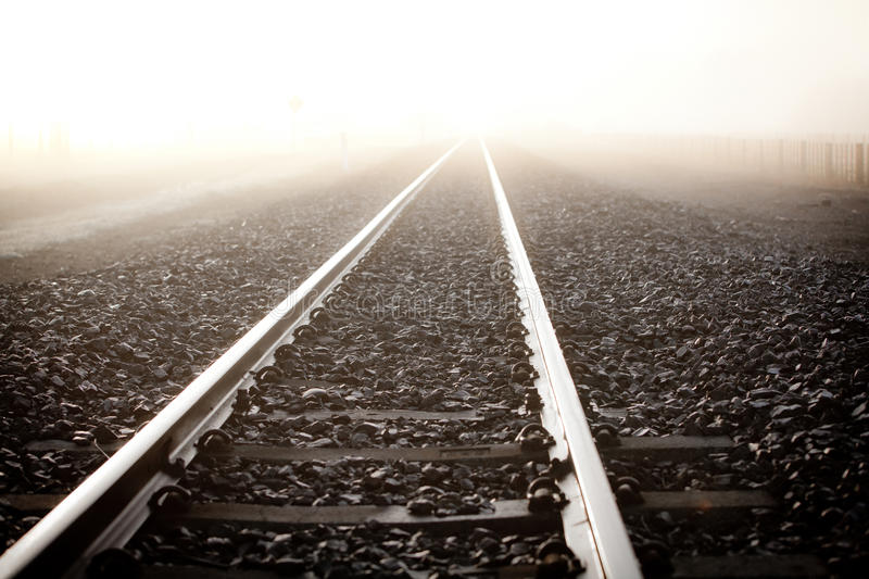 Railroad. Rails disappear in the bright fog stock image