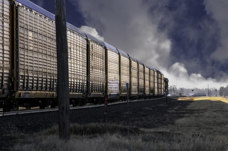 Railroad autoracks hauling new cars to dealers. A train hauling new cars in autoracks to be delivered to dealers. They are coming into a small town early as the royalty free stock image