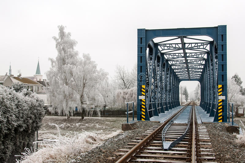 Railroad bridge in Litovel amongst the frost frosted trees in cold winter day stock image