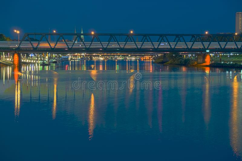 Railroad bridge over river Weser at night with train rushing by royalty free stock images