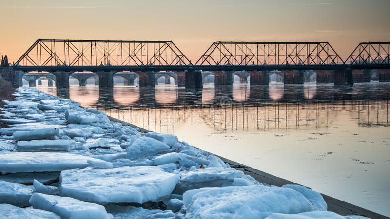 Railroad bridge over the Susquehanna River and ice-filled sidewalk in Harrisburg, PA in winter. Sunrise in Harrisburg, PA with  a railroad bridge over the stock photography