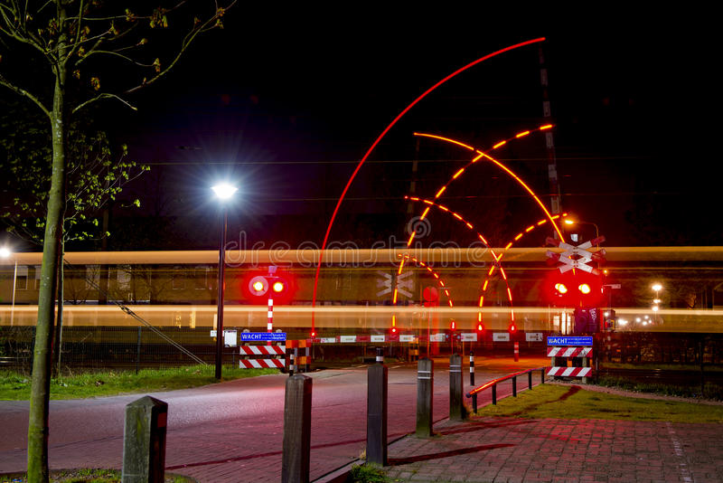 Railroad crossing at night stock photography