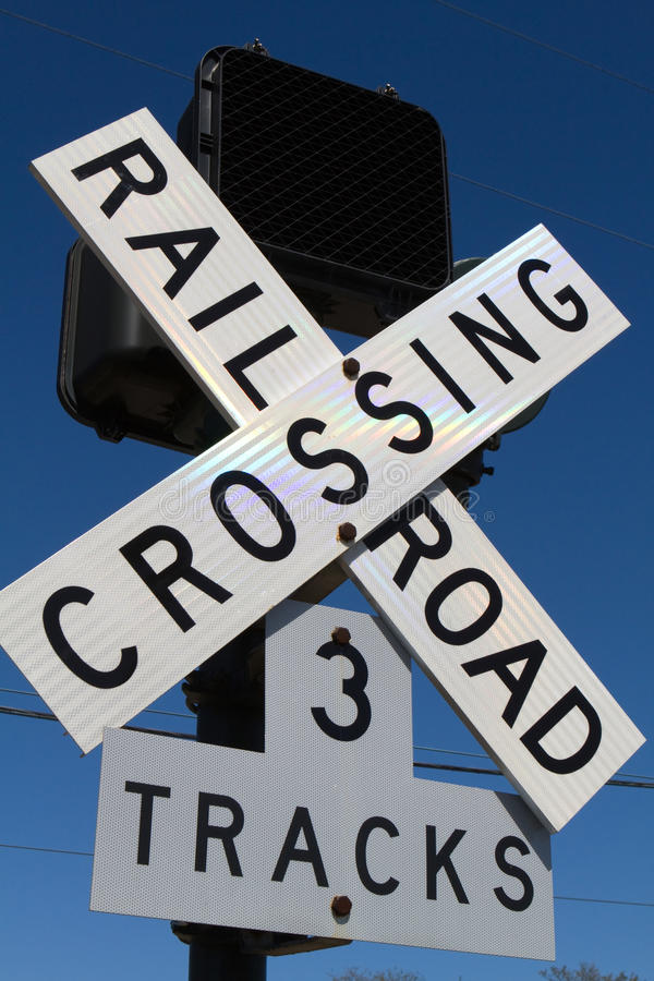 Railroad Crossing Sign. With three tracks against a blue sky royalty free stock images