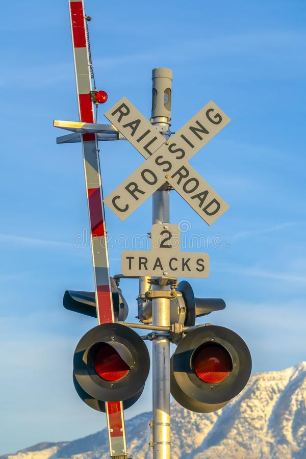 Railroad crossing sign with barrier and red lights. A two tracks railroad crossing sign against snow caped mountain and blue sky. A railroad barrier and red royalty free stock images