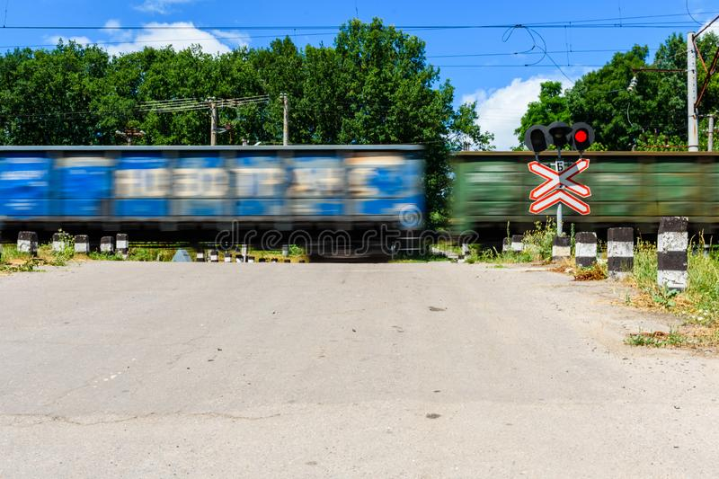 Railroad crossing sign and blinking semaphore in front of the railroad crossing. Blurred motion of the train. Railroad crossing sign and blinking semaphore in royalty free stock photo
