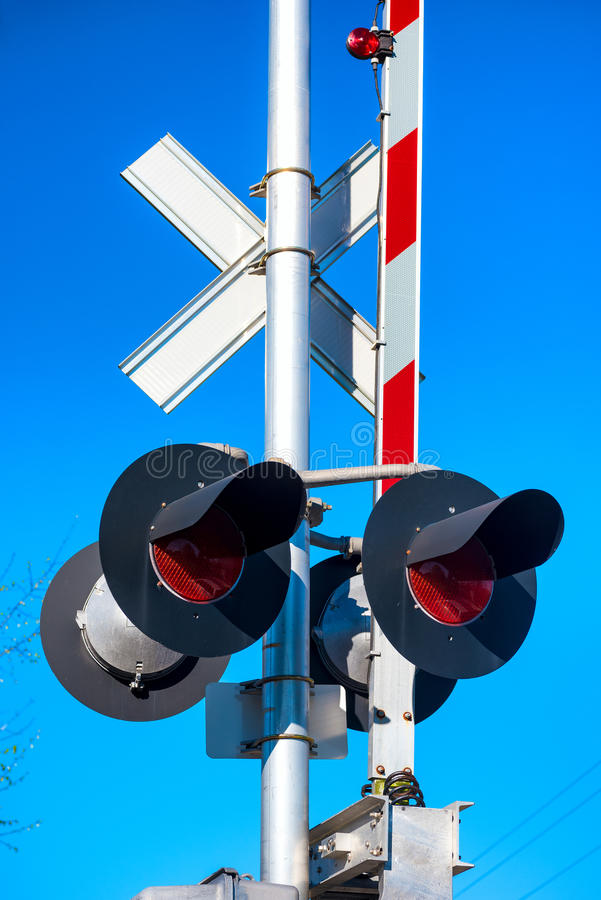 Railroad gate. Closeup of a railroad gate and signal against a bright blue sky stock photography