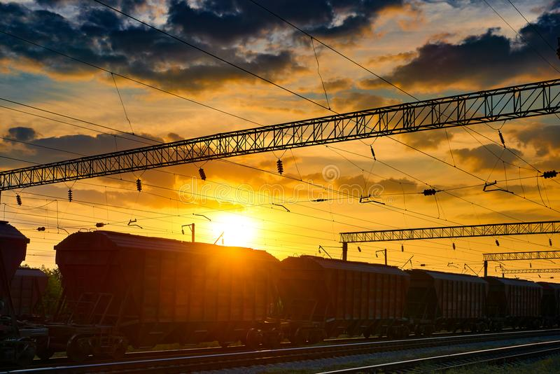 Railroad infrastructure during beautiful sunset and colorful sky, railcar for dry cargo, transportation and industrial concept royalty free stock photos